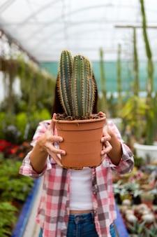 Testa della copertura della donna con il vaso del cactus