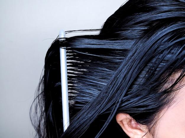 Testa di asiatico con lunghi capelli neri, pettinatura dei capelli con spazzola per capelli. salute dell'attaccatura dei capelli.
