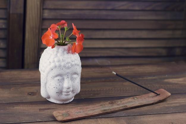 Testa di buddha con fiore, bastone di incenso su un fondo di legno