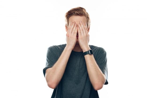 Testa di copertura scioccata del giovane con la mano