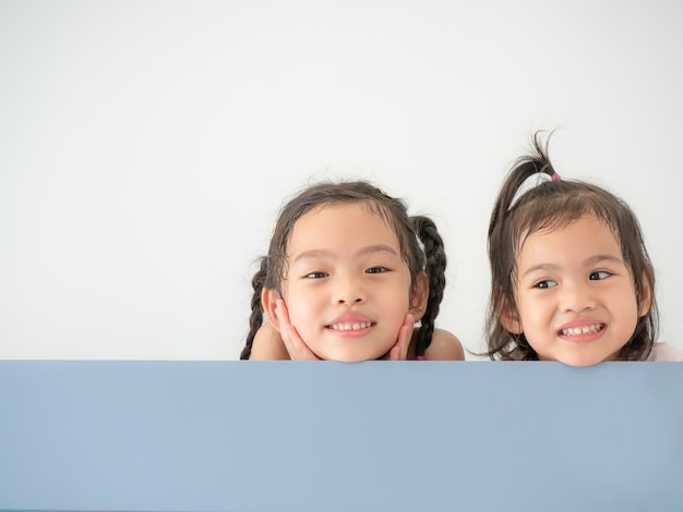Testa di felice ragazza carina asiatica due sorridente sul bordo