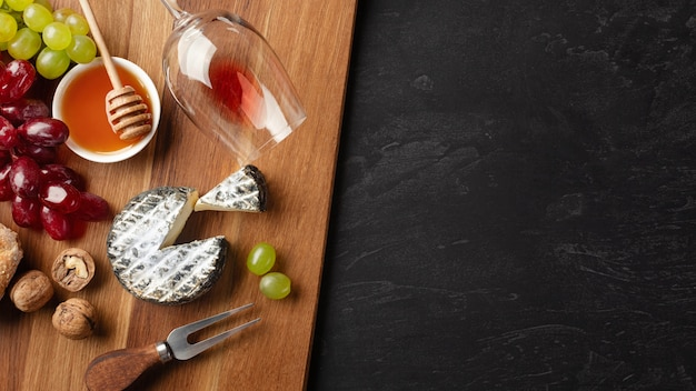 Testa di formaggio, grappolo d'uva, miele, noci e bicchiere di vino su tavola di legno