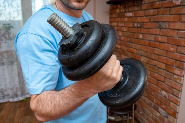 Testa di legno nella mano dell'uomo che fa alto vicino di esercizio di sport di forma fisica a casa