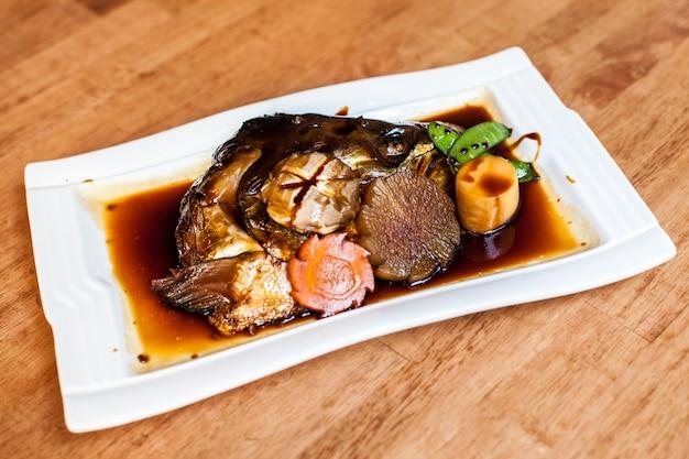 Testa di pesce salmone con salsa stile alimentare giapponese