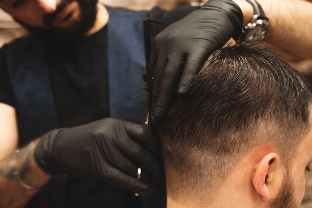 Testa di taglio di capelli nel barbiere, barber taglia i capelli sulla testa del cliente.