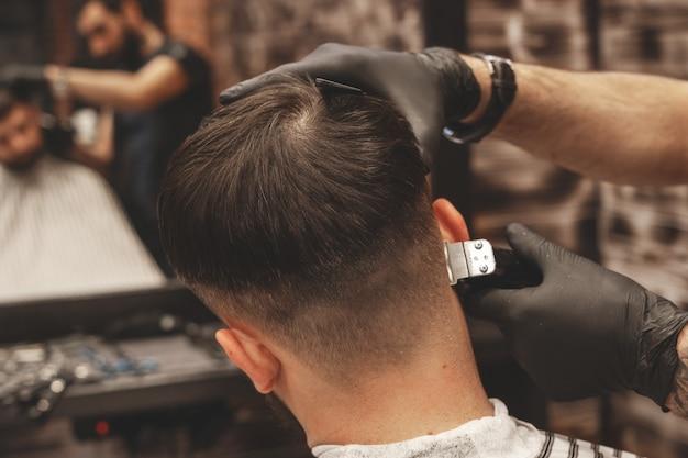 Testa di taglio di capelli nel barbiere. il barbiere taglia i capelli sulla testa del cliente