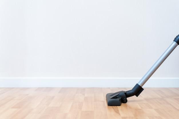 Testa di vuoto moderna sul pavimento di legno con lo spazio della copia, governante che pulisce una stanza usando il vuoto.