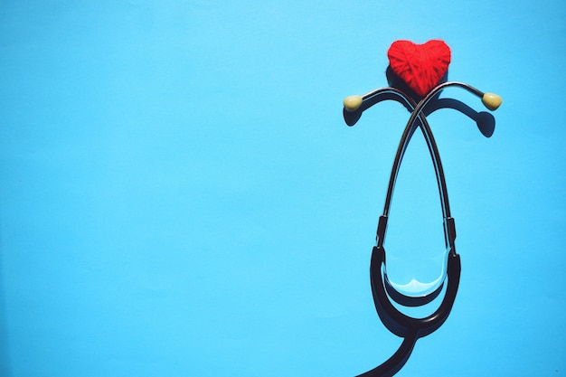 Testa medica dello stetoscopio e cuore rosso sull'azzurro