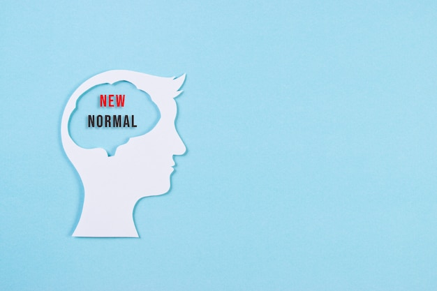 Testa umana in carta tagliata con testo. nuovo concetto normale dopo la pandemia di covid-19. copia spazio.