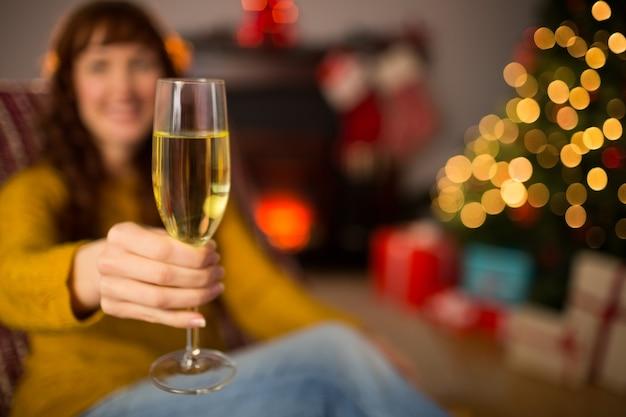 Testarossa che tiene vetro di champagne sullo strato a natale