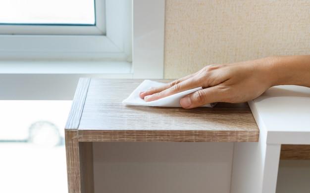 Testata di pulizia della mano della donna con la salvietta disinfettante e lo spruzzo di alcool in camera da letto a casa. concetto di disinfezione di superfici da batteri o virus. avvicinamento