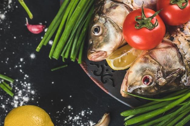 Teste di pesce con erbe aromatiche, limone e pomodori con sale marino intorno