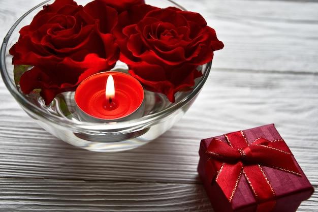 Teste di rose e una candela accesa in una ciotola con acqua e un contenitore di regalo su un bianco in legno. concetto di san valentino