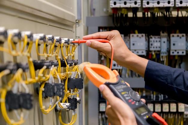 Tester di ingegnere che misura la tensione e la corrente nel controllo elettrico dell'armadio
