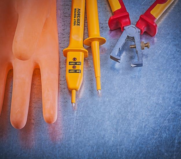Tester elettrico degli spogliarellisti dell'isolamento dei guanti sulla tavola metallica, concetto di elettricità