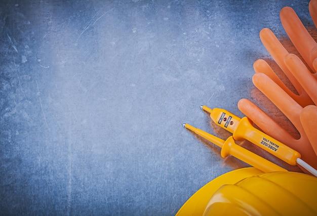 Tester elettrico del casco protettivo dei guanti isolanti sulla versione orizzontale della tavola metallica