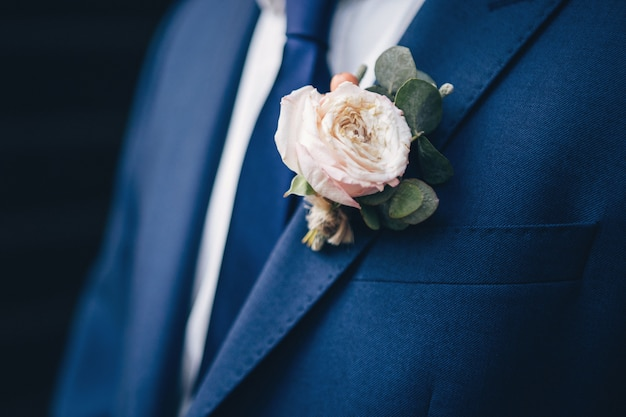 Testimoni dello sposo alla moda che aiutano sposo felice che si prepara al mattino per la cerimonia di nozze. uomo di lusso in tuta in camera. giorno del matrimonio.