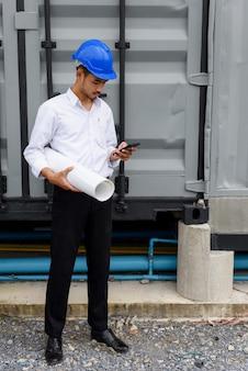 Testo arabo dell'ingegnere sul telefono al cantiere