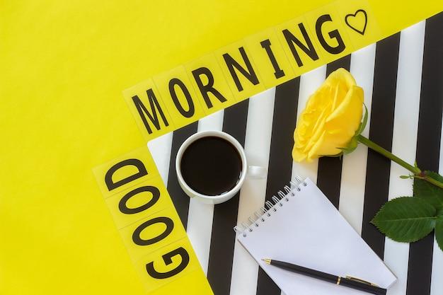 Testo buongiorno, tazza di caffè, ciambella, rosa, blocco note concept elegante posto di lavoro