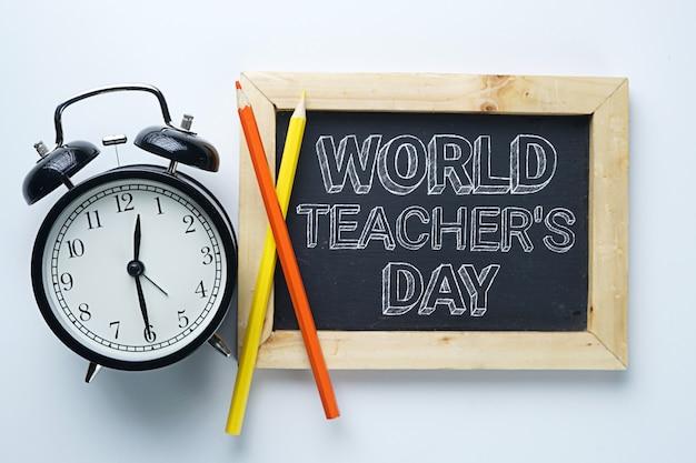 Testo del giorno dell'insegnante mondiale. sveglia, matita colorata e lavagna su sfondo bianco
