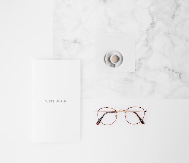 Testo del notebook su carta; tazza di caffè e occhiali sul contesto di texture bianca