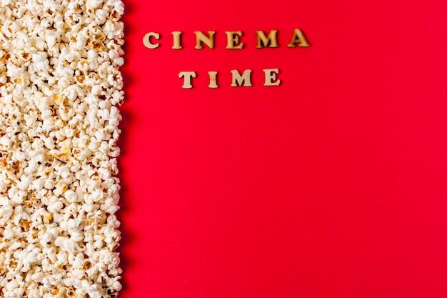 Testo del tempo del cinema vicino ai popcorn su sfondo rosso
