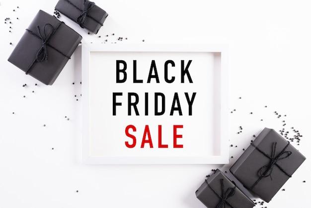 Testo dell'insegna di vendita di black friday sulla cornice bianca con il contenitore di regalo nero.