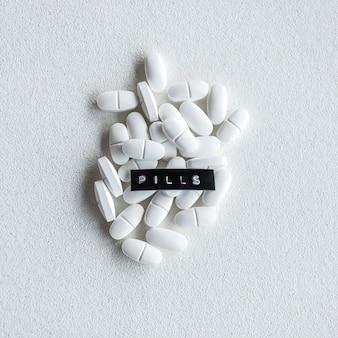 Testo delle pillole sopra le compresse ovali di bianco su fondo ruvido