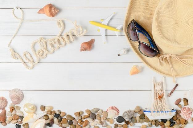 Testo di benvenuto con accessori estivi, sandali e conchiglia