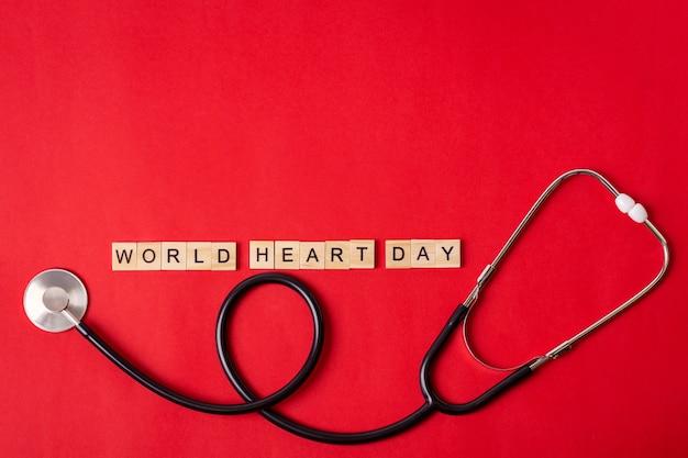 Testo di giornata mondiale del cuore con lo stetoscopio sul rosso