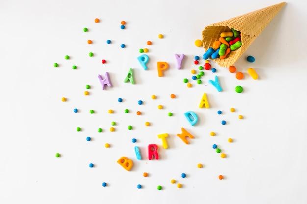 Testo di giorno di nascita felice con caramelle che si rovesciano dal cono gelato della cialda