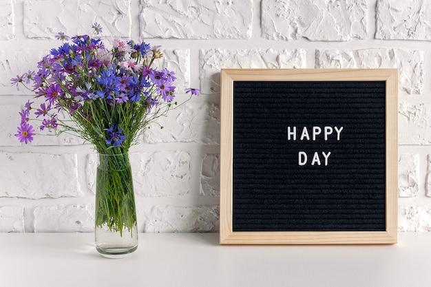 Testo di giorno felice sul bordo di lettera nero e sui fiori blu del mazzo in vaso sulla tavola contro il muro di mattoni bianco