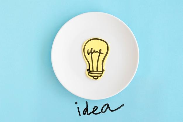 Testo di idea sotto il piatto bianco con la lampadina disegnata a mano