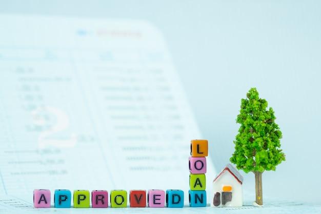 Testo di prestito e piccola casa modello e piccolo albero con notebook