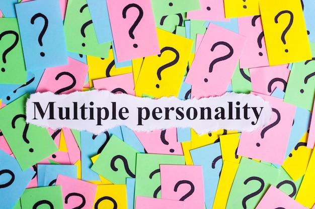 Testo di sindrome di personalità multipla su bigliettini colorati contro i punti interrogativi