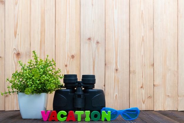 Testo di vacanza e binocolo su legno