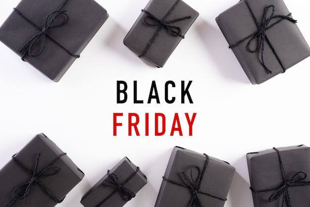 Testo di vendita di black friday con il contenitore di regalo nero su bianco