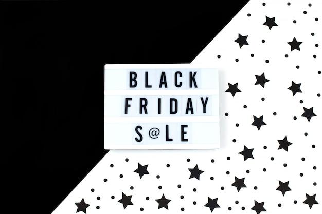 Testo di vendita di black friday su lightbox bianco e priorità bassa dell'insegna delle stelle nere