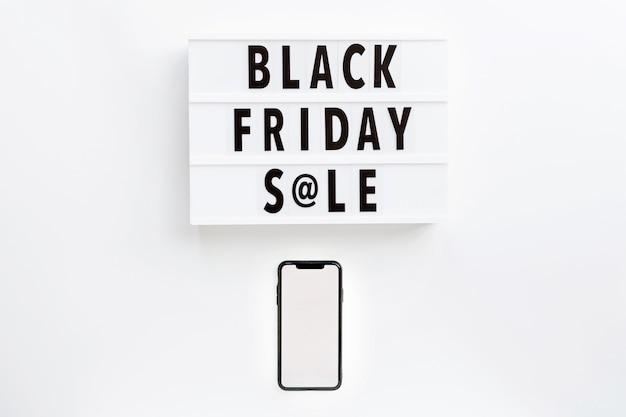 Testo di vendita di black friday su lightbox e telefono cellulare su fondo bianco