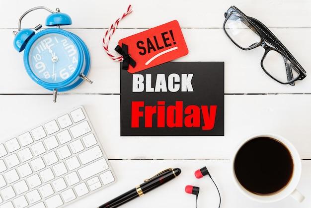 Testo di vendita di black friday sull'etichetta rossa e nera con gli accessori dell'ufficio sulla tavola di legno bianca
