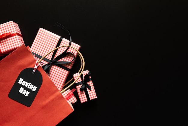 Testo di vendita di giorno di inscatolamento su un'etichetta nera con il sacchetto della spesa e contenitore di regalo su fondo nero