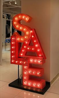 Testo di vendita illuminato con lampadine in negozio.