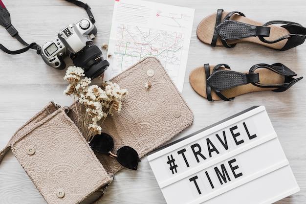 Testo di viaggio e tempo con accessori femminili sulla scrivania in legno