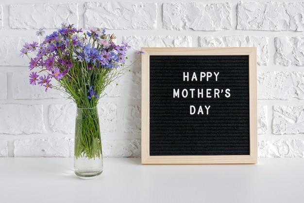 Testo felice di giorno di madri sulla bacheca nera e sui fiori blu del mazzo in vaso sulla tavola contro il muro di mattoni bianco.