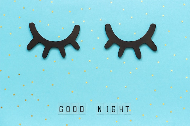 Testo good night, ciglia nere di legno, occhi chiusi, stella d'oro. concetto sogni d'oro saluto
