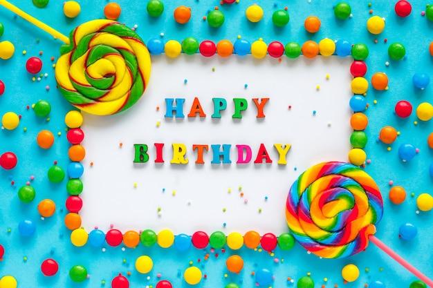 Testo happy birthday, biglietto di auguri, caramelle e lecca lecca,