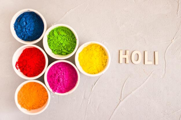 Testo holi vicino al diverso tipo di colore in polvere su sfondo concreto