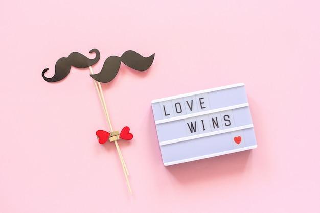 Testo l'amore vince e accoppia i puntelli di carta dei baffi su fondo rosa