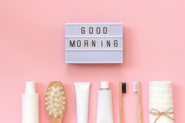 Testo light box buongiorno e set di prodotti cosmetici e strumenti per la doccia o il bagno su sfondo rosa