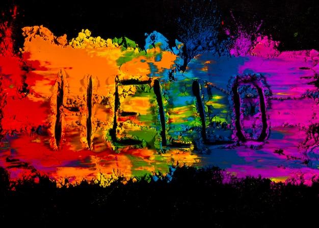 Testo scritto a mano ciao sul colore di polvere colorata holi su sfondo nero